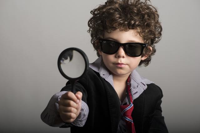 サングラスをかけた外人の子供が虫眼鏡をもっている画像