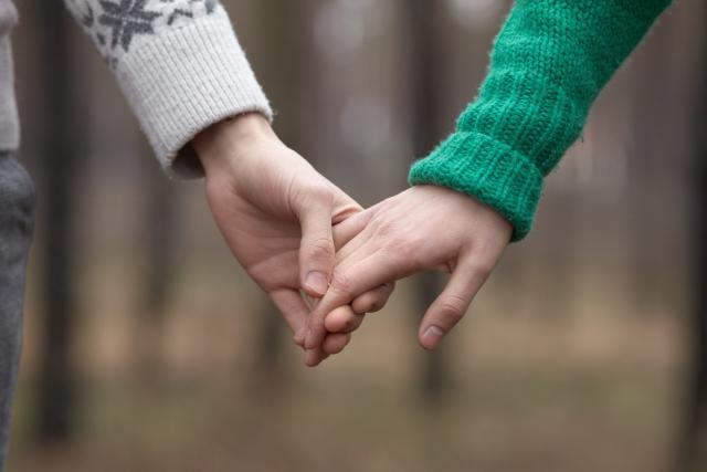 手を繋いでいるカップルの画像