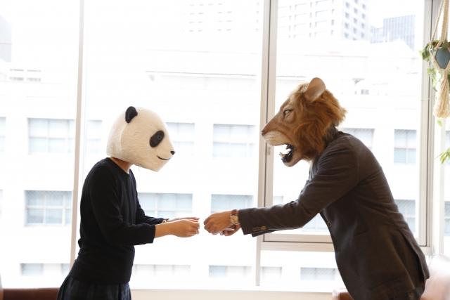 人から認められるように頑張っている動物の被り物をしている二人が名刺を交換している画像