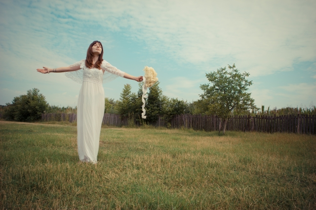 野原で女性が大きく手を広げてる画像