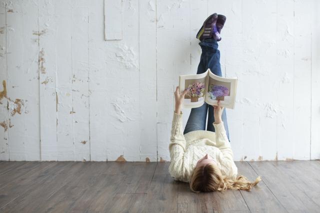 心が満たされず寝っ転がりながら本を見ている外人女性の画像