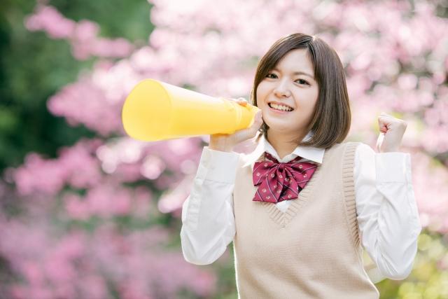 桜の前で感情をぶちまけようとしている女性の画像