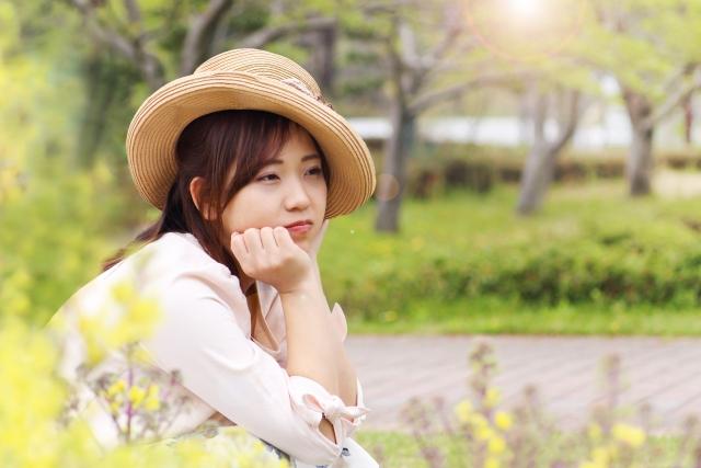 凹んだ気持ちを花を見て癒されている帽子をかぶった女性の画像