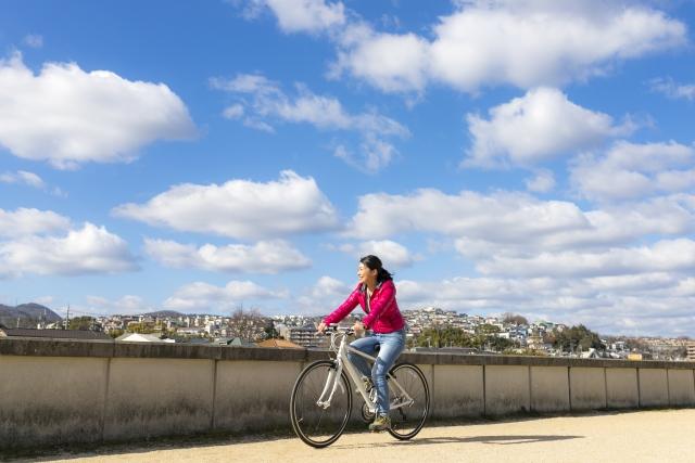 一人でサイクリングをして楽しそうにしている女性の画像