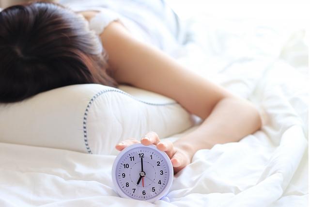 寝ている女性が目覚ましに手をかけている画像