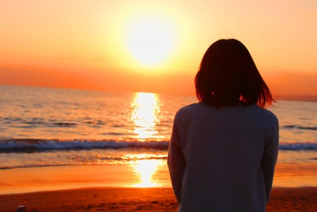 毎日同じことの繰り返しの日々で疲れを夕日を見て癒している女性の画像