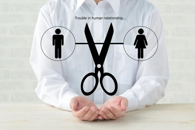ハサミで人間関係を断捨離しようとしているシャツ姿の男性のイメージ画像