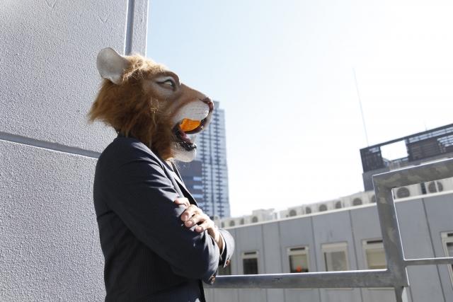 人生つまらない孤独と感じて黄昏ているライオンの被り物をしたスーツ姿の男性の画像