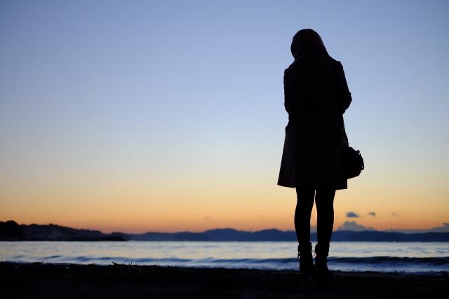 海辺で一人で立ち眺めている女性のシルエットの画像