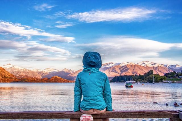 人生つまらないニート生活に嫌気をさして自然な湖を眺めている帽子をかぶった男性の画像
