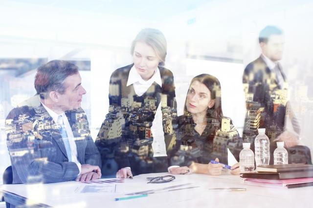 仕事慣れない4人の社員が話し合いしている画像