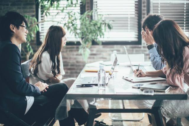会社で4人の男女がパソコン開いて会議している画像