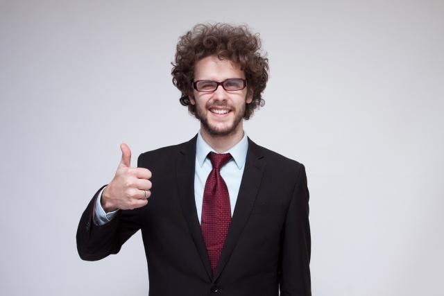 親指を立ててはにかんでいるスーツ姿の外人男性の画像