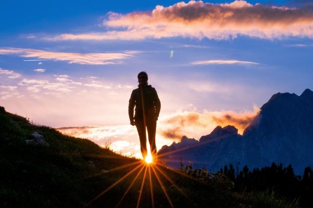 朝陽が昇るところを見ている男性の後ろ姿の画像