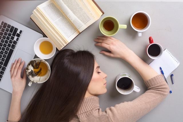 人のために頑張りすぎて疲れてテーブルで寝ている女性の画像