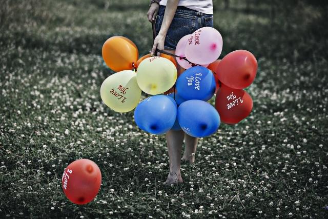 複数の風船を持っている女性の画像