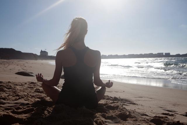 朝日に照らされながら海でヨガをしている女性の画像