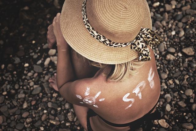 自分が気持ち悪いと悲観してしゃがんでいる帽子をかぶった女性の画像