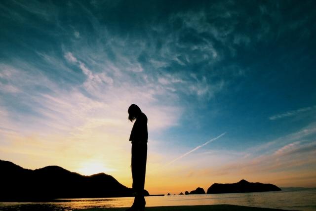 夕焼け海辺で下向きで立っている人の画像