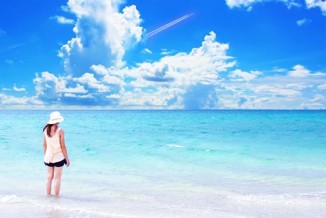 海で白いワンピースを着た女性が立っている女性の画像