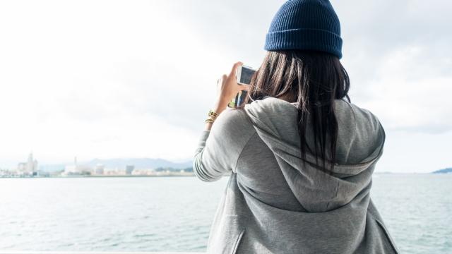 嫉妬について考えている女性が海をカメラで撮っている画像