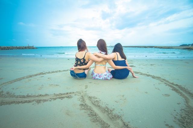 海で信用が深い3人の女性が肩を組んで座っている画像