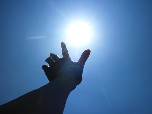 太陽に手を差し伸べている画像