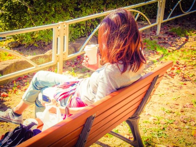 自分の嫌いなところを考えて落ち込んでいるベンチに座っている女性の画像