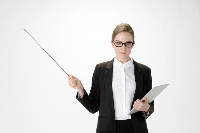価値観は違うと物差しで指導しているスーツ姿の女性の画像