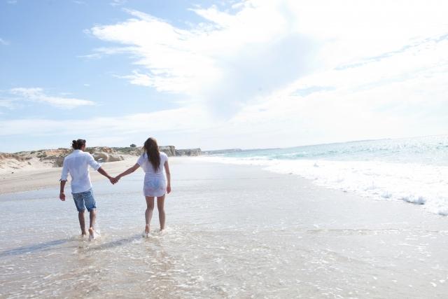 海の浜辺で手を繋いで歩いているカップルの画像