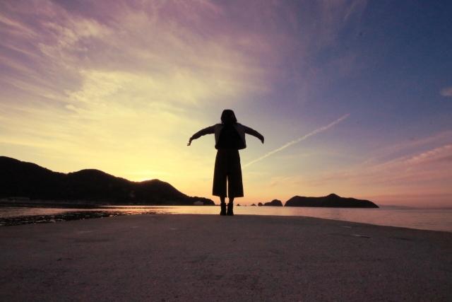 夕焼けの海岸で女性が腕を広げて立っている画像