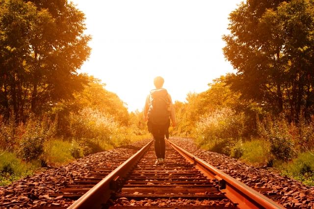 自由に生きると決意し夕焼けをバックに線路の真ん中を歩いている男性の画像