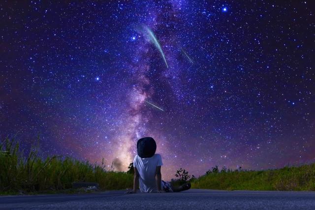 生きている意味がわからないと悩んでいる男性が星空を眺めている画像