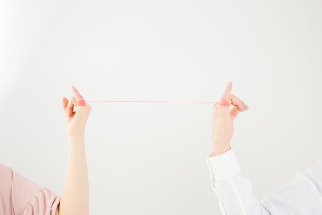 運命の赤い糸をカップルが小指にひっかけている画像