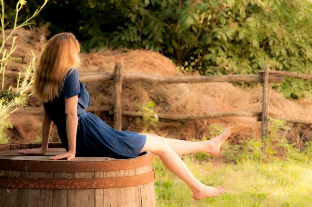 人生について悩んでいる女性が樽の上でのんびりしている画像
