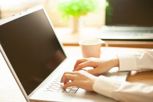 パソコンでブログを書いている女性の画像