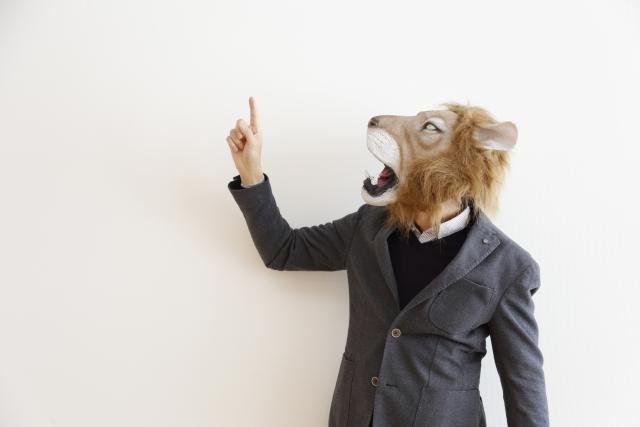 ライオンの被り物をしているスーツ姿の男性が、ブログのタイトルの書き方を指導している様子の画像
