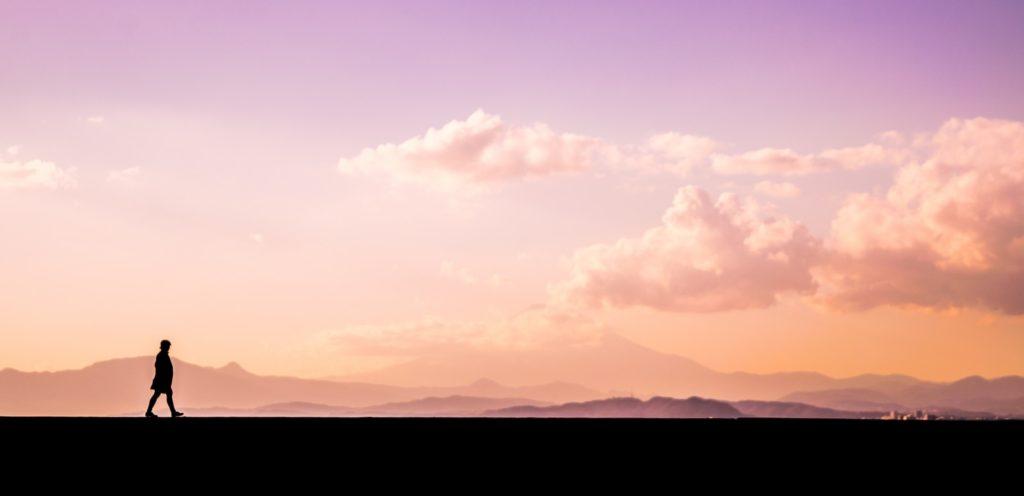 夕焼けの土手を歩いている男性のシルエット画像