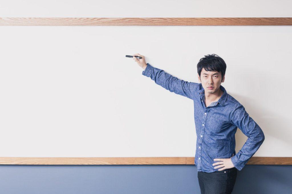 フリーランスで成功する方法を黒板を指さし指導している男性の画像