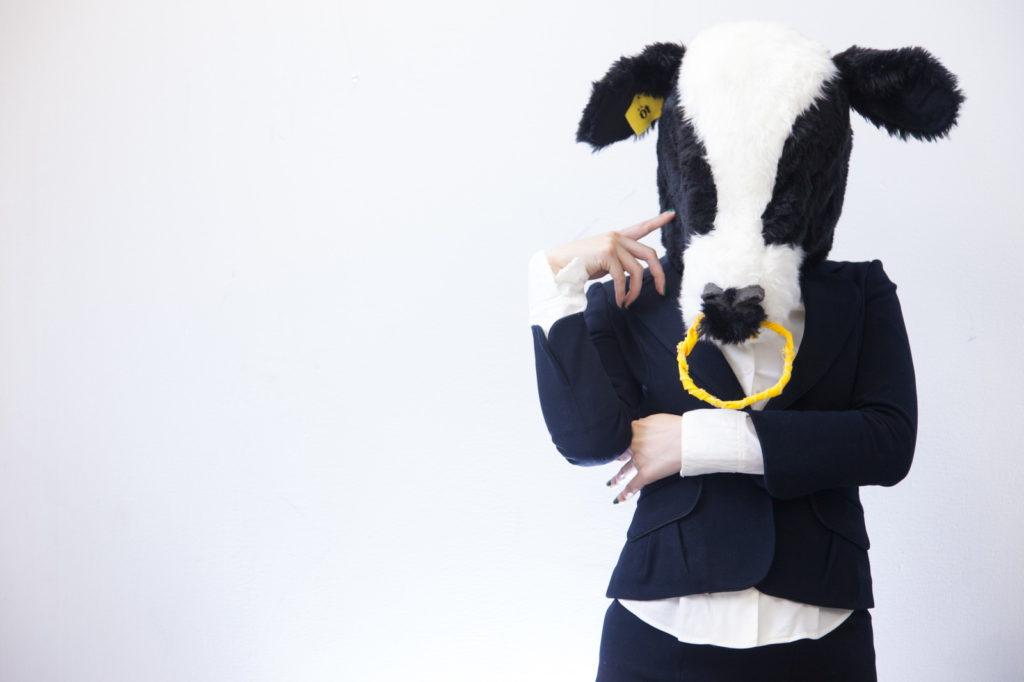 牛の被り物している女性が考え事をしている画像