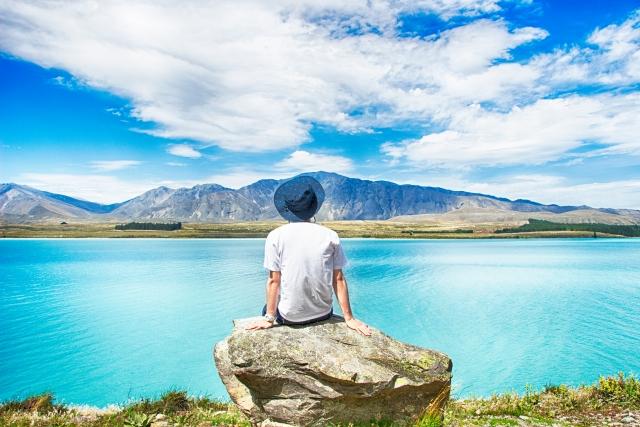 フリーランスになったけど仕事がないと落ち込んで湖を眺めている男性の画像