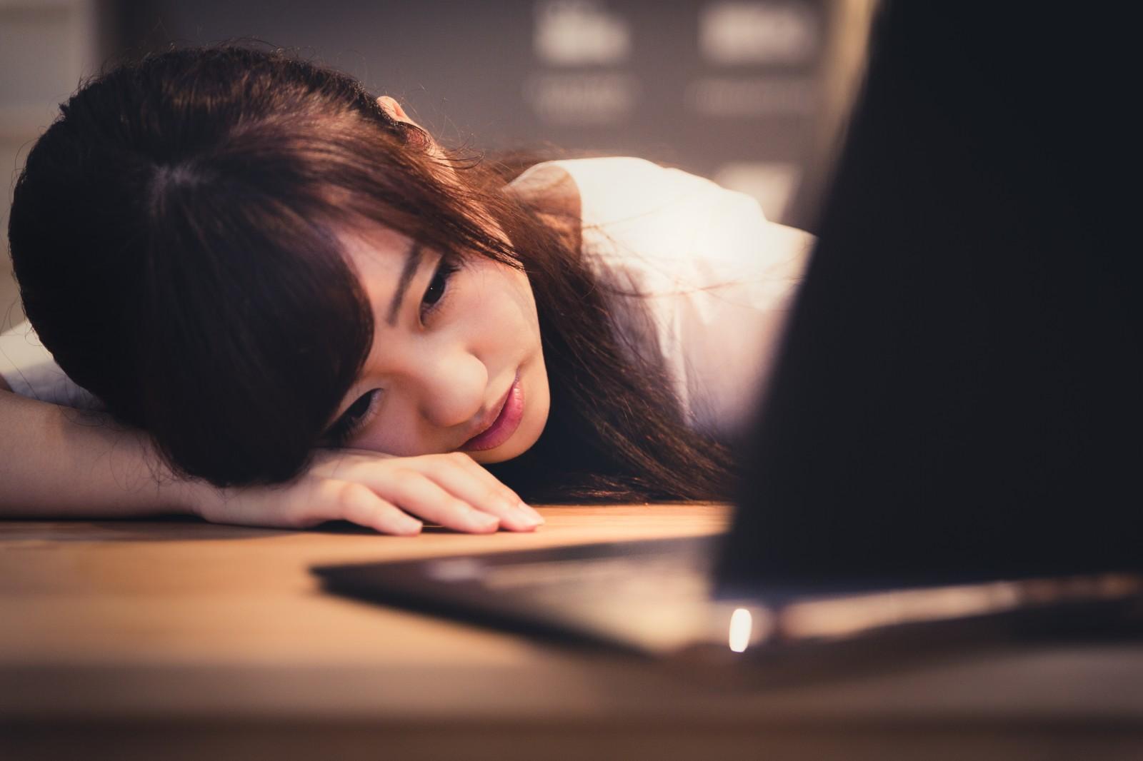 フリーランスになって失敗しそうで挫けそうにパソコンを眺めている女性の画像