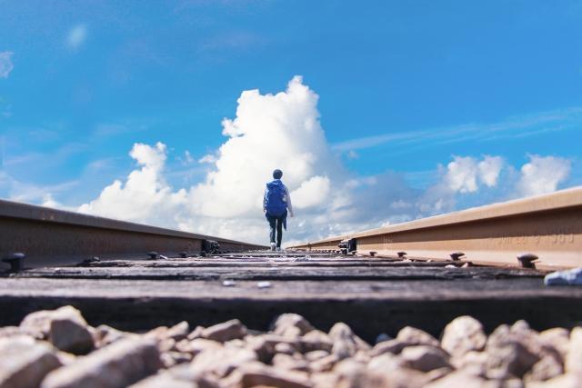 線路の真ん中を歩く男性の画像