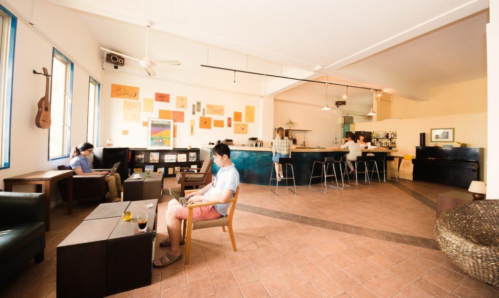 広いカフェでパソコンで仕事している男性の画像