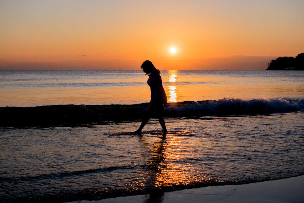 夕焼けの海辺を散歩している女性の画像