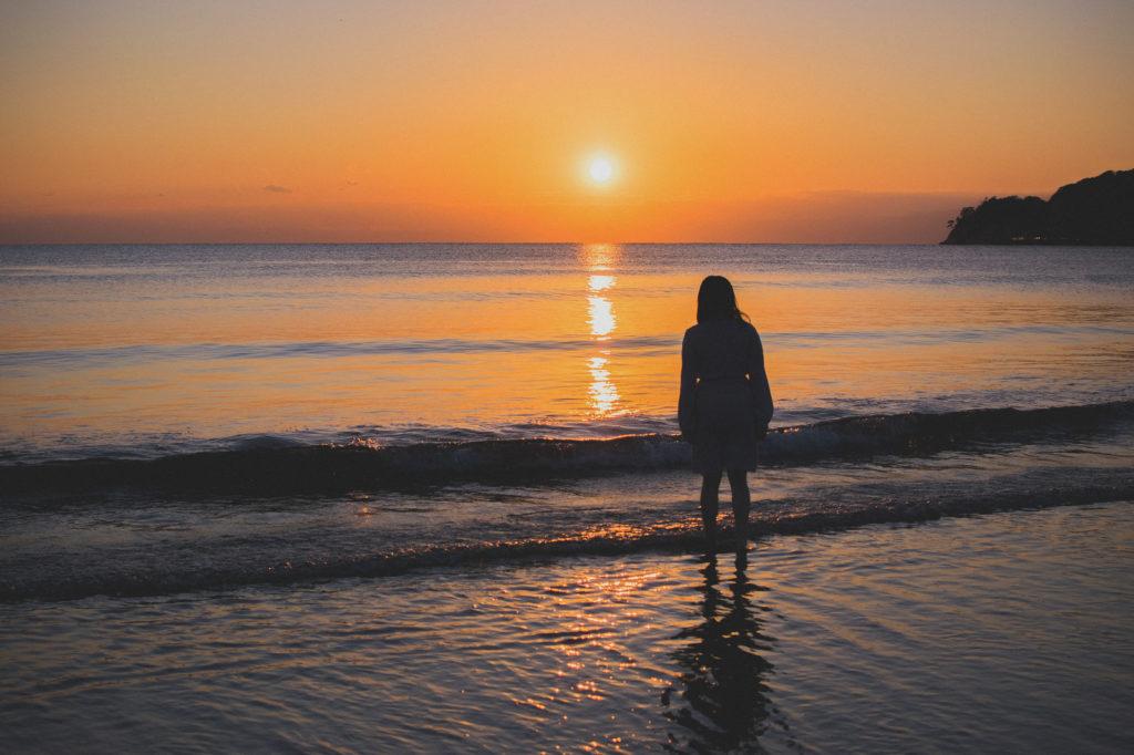 海辺の夕日を眺めている人のシルエットの画像