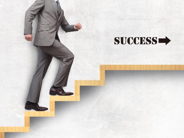 successと書かれた階段を歩いているスーツ姿の男性の画像