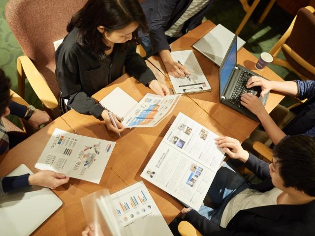 資料を見て会議をしている会社員たちの画像