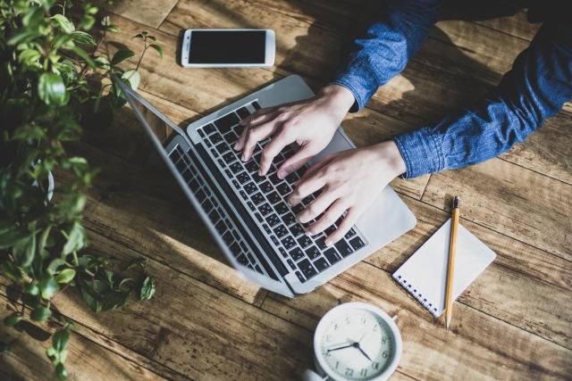 フリーランスのメリットをパソコンでまとめている男性の画像