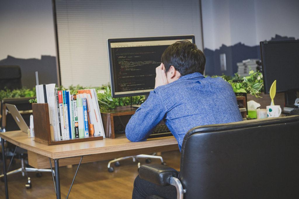 パソコンの前で、頭を抱えている男性の画像